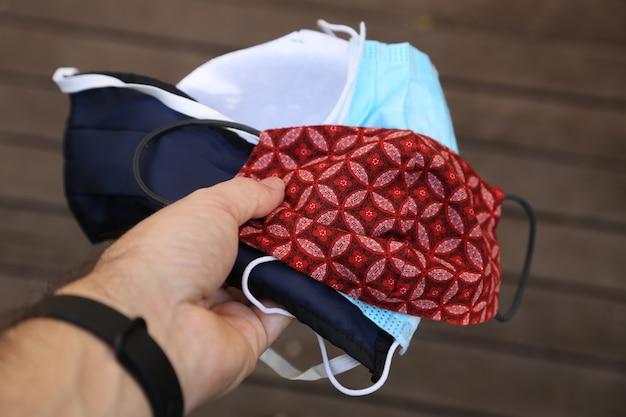 Selektywne fokus strzał męskiej dłoni trzymającej kolorowe maski na twarz