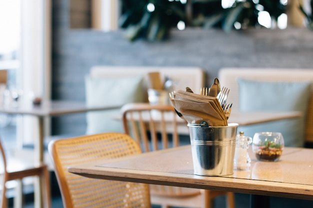 Selektywne fokus strzał wiadra z widelcami i serwetkami na modnym stoliku kawiarnianym