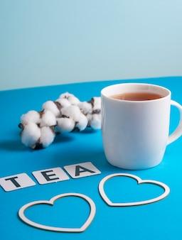 Selektywne skupienie: czarna herbata cejlońska w białym kubku na niebieskim zwykłym, copyspace. tekturowe litery ułożone w angielskim słowie tea