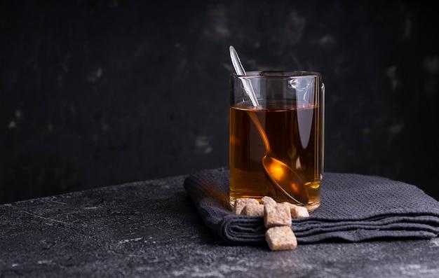 Selektywne skupienie: czarna herbata cejlońska w przezroczystym kubku na ciemnym stole. copyspace. pozycja pozioma. minimalistyczny styl
