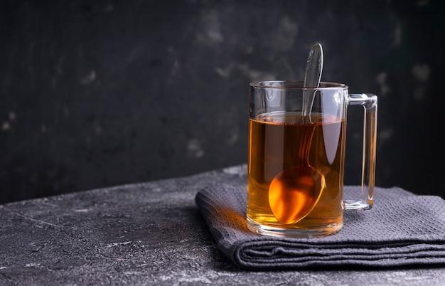 Selektywne skupienie: czarna herbata cejlońska w przezroczystym kubku na stole. copyspace. pozycja pozioma. minimalistyczny styl