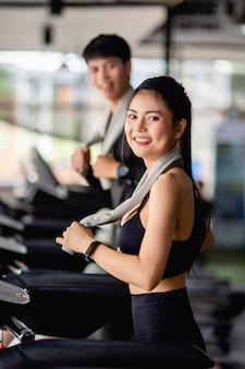 Selektywne skupienie, młoda seksowna kobieta ubrana w odzież sportową i smartwatch, niewyraźny młody mężczyzna, biegną na bieżni do treningu w nowoczesnej siłowni, uśmiech,