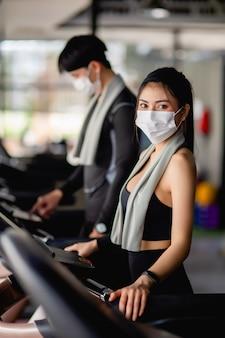Selektywne skupienie, młoda seksowna kobieta w masce ubrana w odzież sportową i smartwatch oraz niewyraźny młody mężczyzna, stoją ustawienie programu na bieżni do treningu w nowoczesnej siłowni, kopia przestrzeń