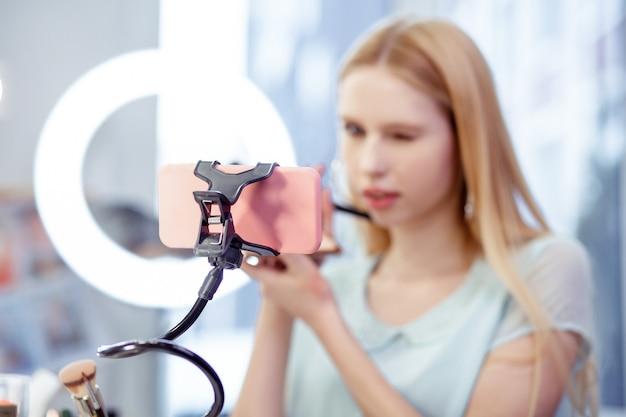 Selektywne skupienie nowoczesnego różowego smartfona używanego do nagrywania wideo
