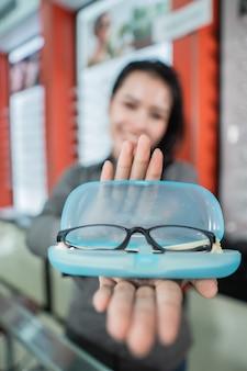 Selektywne skupienie okularów w pudełku okularowym na tle pięknej uśmiechniętej kobiety w optyce