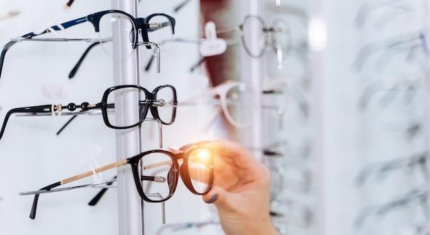Selektywne skupienie pod ręką. kobieta dotyka okularów korekcyjnych na stoisku z okularami. szeroki asortyment w sklepie.