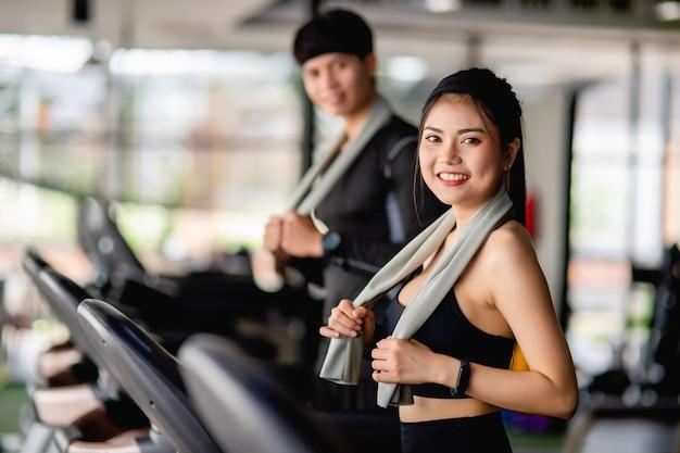Selektywne skupienie, portret seksowna kobieta w odzieży sportowej, bieganie na bieżni, niewyraźny przystojny mężczyzna biegnący prawie, ćwiczą w nowoczesnej siłowni fitness, uśmiech, kopia przestrzeń