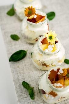 Selektywne skupienie pysznych i słodkich lodów waniliowych w szklanych słoikach ozdobionych żółtymi kwiatami