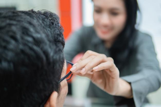 Selektywne skupienie ręki kobiety w sklepie pomaga mężczyźnie założyć okulary podczas siedzenia, przymierzając okulary u optyka