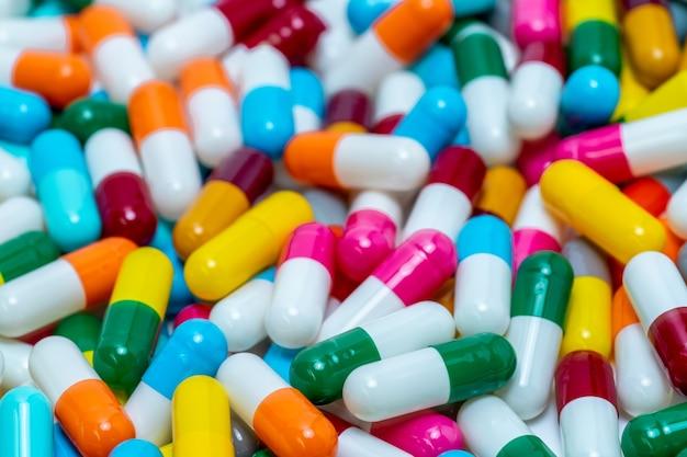 Selektywne skupienie się na antybiotykowych tabletkach w kapsułkach. oporność na antybiotyki. kupie kapsułki w jasnych kolorach.