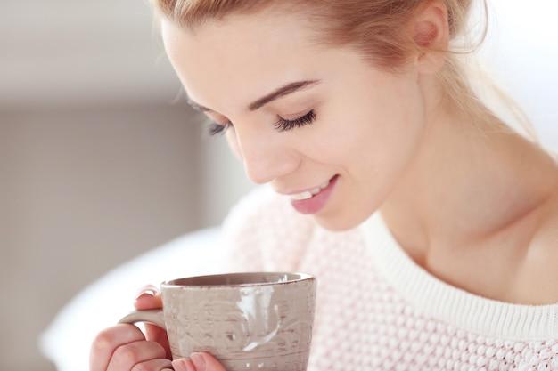 Selektywne skupienie się na blond pięknej uśmiechniętej dziewczynie cieszącej się filiżanką gorącej pysznej kawy