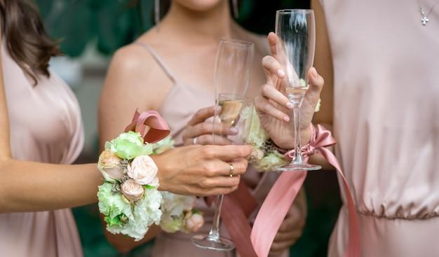 Selektywne skupienie się na dłoniach druhen w różowych jedwabnych sukienkach ozdobionych naturalnymi kwiatami i kieliszkami szampana
