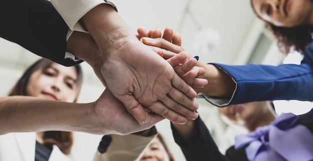 Selektywne skupienie się na dłoniach wielu kobiet biznesu w formalnych garniturach zebranych podczas spotkania biznesowego z rozmytymi twarzami w tle. koncepcja spotkania biznesowego.