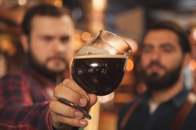Selektywne skupienie się na kuflu piwa w rękach producentów piwa.