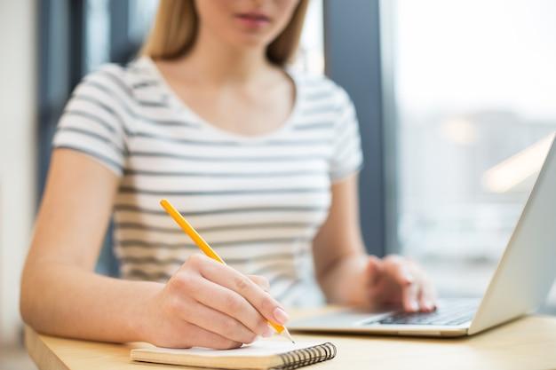 Selektywne skupienie się na małym notesie używanym przez miłą, pozytywną młodą kobietę do robienia notatek