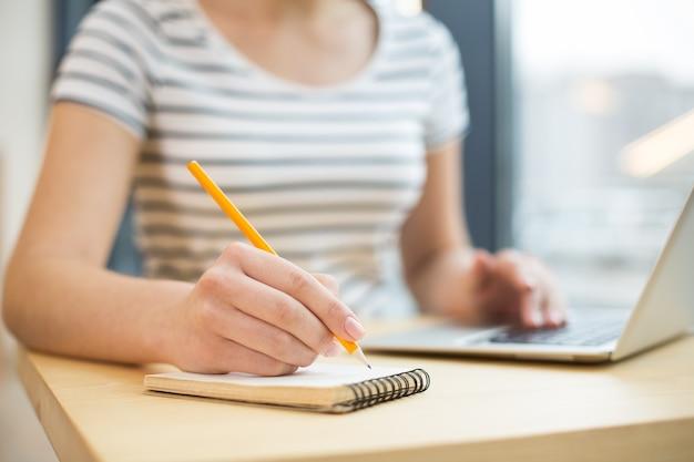 Selektywne skupienie się na notatniku leżącym na stole i używanym do robienia notatek
