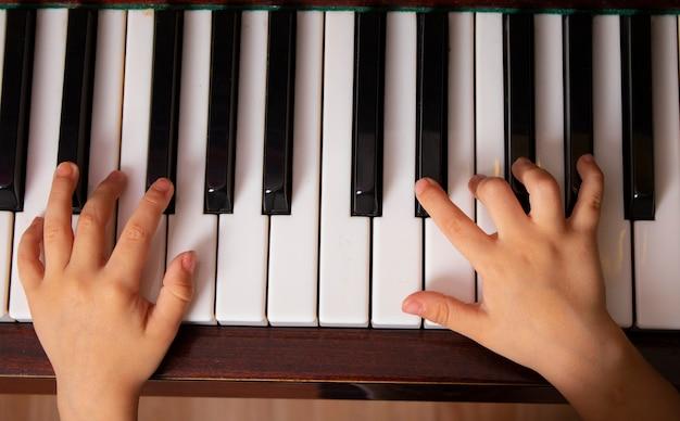 Selektywne skupienie się na palcach dzieci na fortepianie z widokiem z góry na naukę muzyki