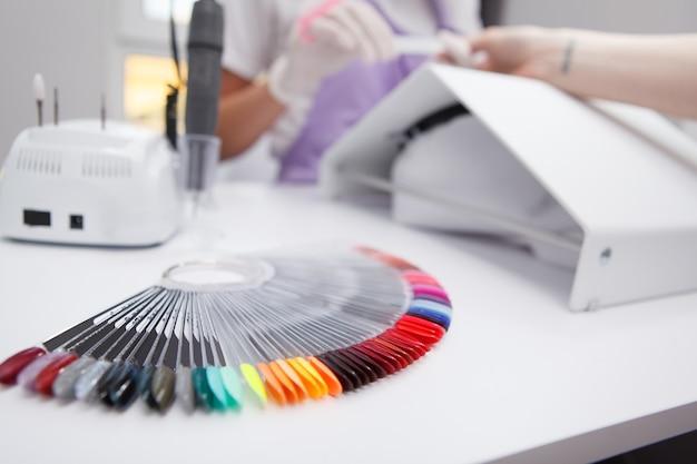 Selektywne skupienie się na palecie kolorów lakieru do paznokci, profesjonalna manikiurzystka pracująca w tle