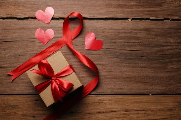 Selektywne skupienie się na pudełku z czerwoną wstążką i papierem w kształcie miłości na rustykalnym drewnianym stole, widok z góry płasko leżał.