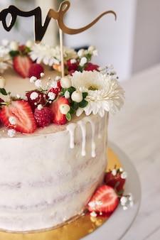 Selektywne skupienie się na pysznym białym torcie weselnym z czerwonymi jagodami, kwiatami i nakładką na ciasto