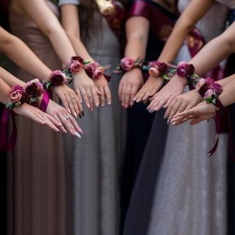 Selektywne skupienie się na rękach grupy dziewcząt z butami. piękne dekoracje kwiatowe na dłonie