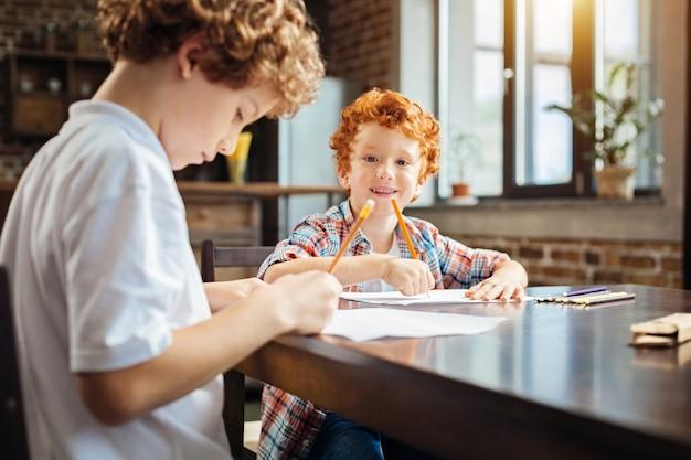 Selektywne skupienie się na rękach pozytywnego rudowłosego dziecka trzymającego ołówek i patrzącego w kamerę na jego twarzy, siedzącego obok starszego brata i rysującego