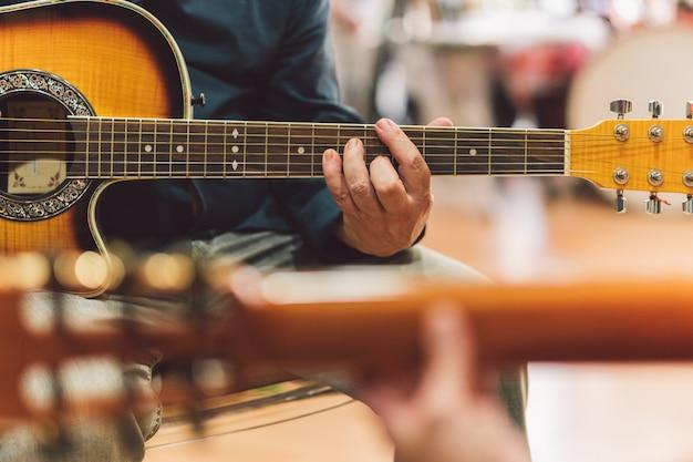 Selektywne skupienie się na rękach starszego mężczyzny grającego na gitarze w duecie z kobietą.