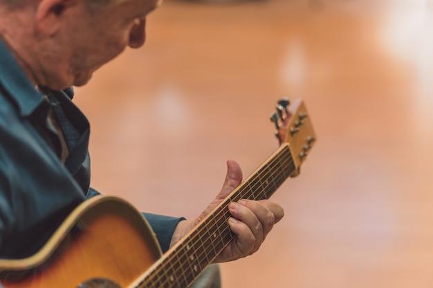 Selektywne skupienie się na rękach starszego mężczyzny grającego na gitarze