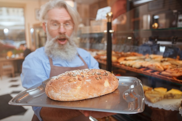 Selektywne skupienie się na świeżo upieczonym pysznym chlebie, który trzyma starszy piekarz