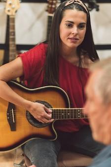 Selektywne skupienie się na twarzy młodej kobiety podczas gry na gitarze ze starszymi mężczyznami