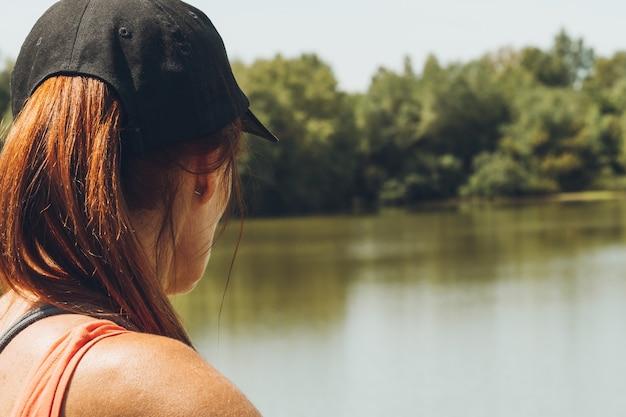 Selektywne skupienie się na tylnej części głowy kaukaskiej kobiety w czapce patrzącej na rzekę i krajobraz.