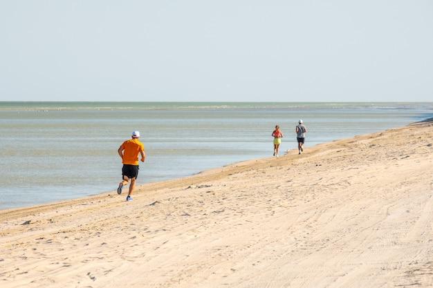 Selektywne skupienie się od tyłu na człowieku biegnącym wzdłuż plaży wzdłuż morza. ćwiczenia sportowe na łonie natury w letni dzień.
