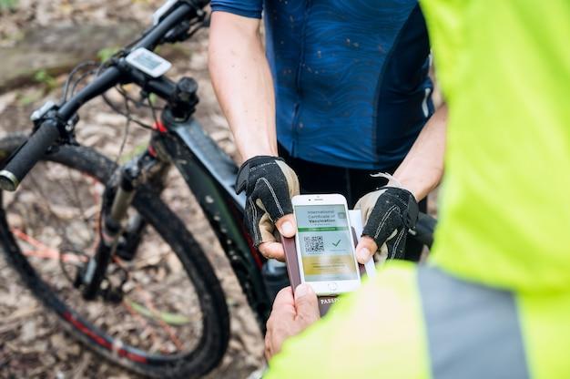 Selektywne skupienie, sportowiec na rowerze górskim pokazuje paszport zdrowia z certyfikatem szczepień przez telefon na torze wyścigowym, aby potwierdzić, że został zaszczepiony przeciwko koronawirusowi. sport podczas pandemii covid-19.