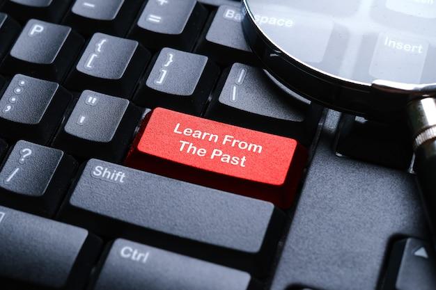 Selektywne skupienie szkła powiększającego na klawiaturze komputera z czerwonym przyciskiem napisane z learn from past. koncepcja biznesowa i finansowa.