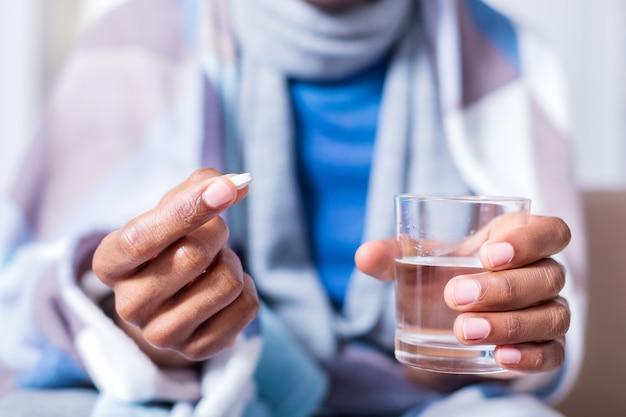 Selektywne skupienie szklanki z wodą i pigułki w rękach miłego chorego człowieka