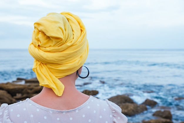 Selektywne skupienie ujęcie młodej kobiety relaksującej się nad morzem