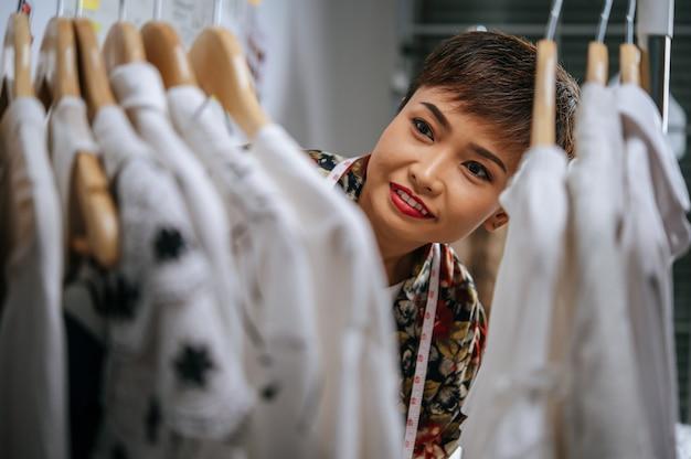 Selektywne skupienie, zbliżenie młodej projektantki, uśmiechniętej kobiety i dumnej ze swojego projektu ubrania na wieszaku, taśma miernicza na szyi