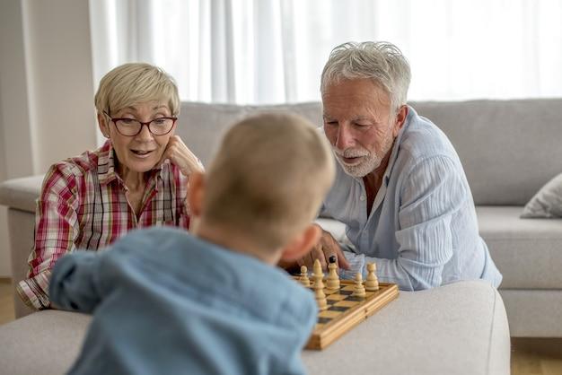 Selektywne ujęcie ostrości babci i dziadka grających w szachy z wnukiem