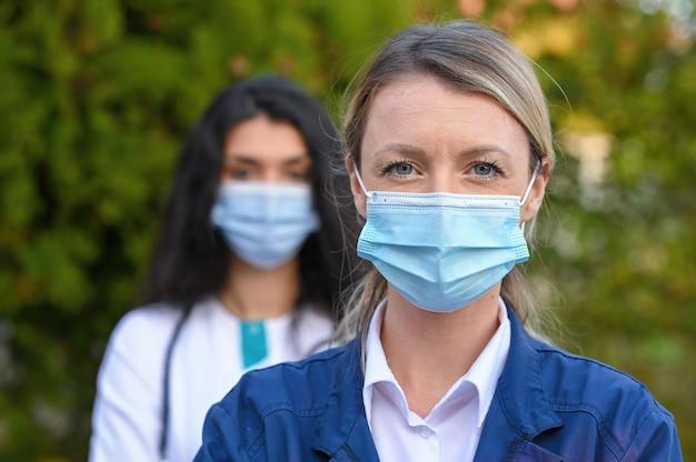 Selektywne ujęcie ostrości lekarzy noszących maski na twarz na zewnątrz