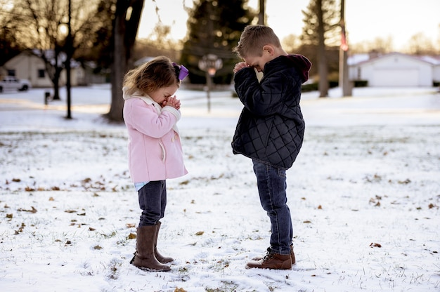 Selektywne ujęcie ostrości ślicznych małych dzieci modlących się w środku parku zimowego