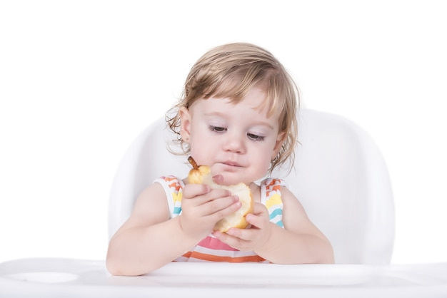 Selektywne ujęcie ostrości szczęśliwej małej dziewczynki jedzącej gruszkę