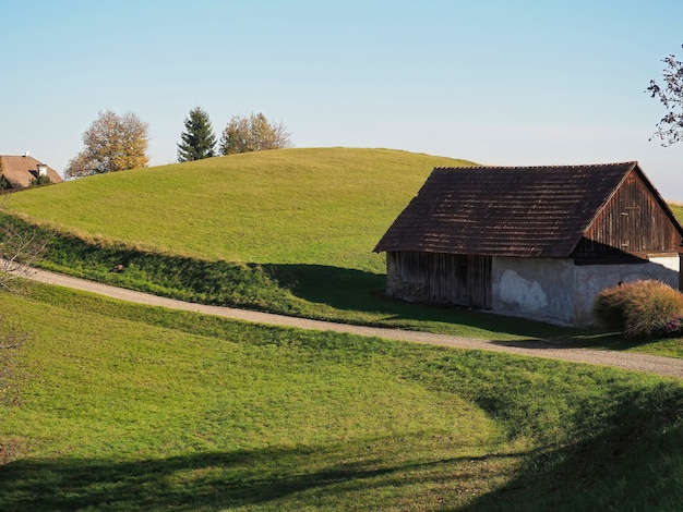Selektywne ujęcie ostrości wiejskiego domu i drzew na wzgórzach w słoneczny dzień