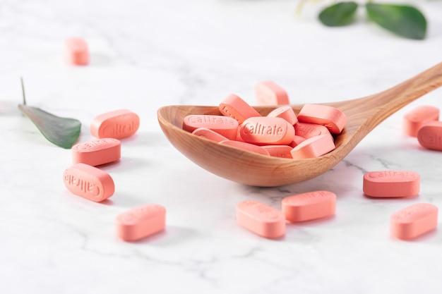 Selektywne ujęcie ostrości wielu tabletek wapnia caltrate w drewnianej łyżce