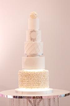 Selektywne ustawianie ostrości. duże królewskie ciasto w białym kolorze ozdobione srebrnymi dodatkami i białą śmietaną na luksusowym ślubie. deser po uroczystej kolacji panny młodej i pana młodego.