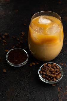 Selektywne ustawianie ostrości, kawa z lodami i śmietaną w wysokiej przezroczystej szklance na ciemnej powierzchni