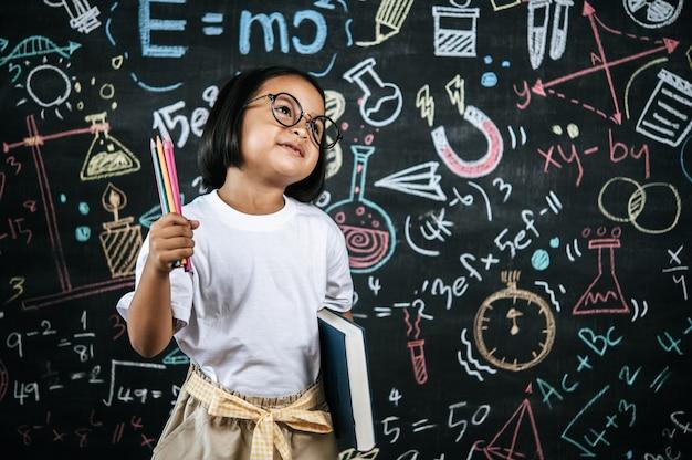 Selektywne ustawianie ostrości, mała dziewczynka w okularach, trzymająca w ręku kolorowy ołówek i trzymająca duży podręcznik