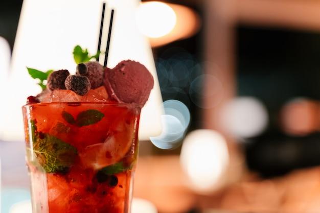 Selektywne ustawianie ostrości w szklance z czerwonym koktajlem ozdobionym jagodami i lodami w nocy