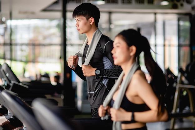 Selektywny fokus młody mężczyzna, niewyraźna młoda seksowna kobieta na pierwszym planie ubrana w odzież sportową i smartwatch, biegną na bieżni do treningu w nowoczesnej siłowni,