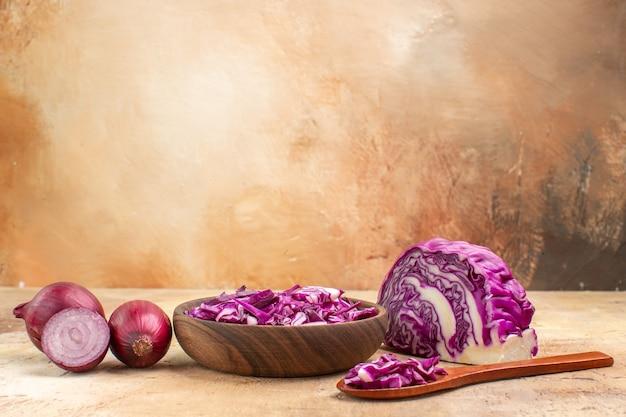 Selektywny widok kilku czerwonej cebuli i posiekanej czerwonej kapusty w drewnianej misce na zdrową sałatkę z buraków na drewnianym stole z wolnym miejscem na tekst