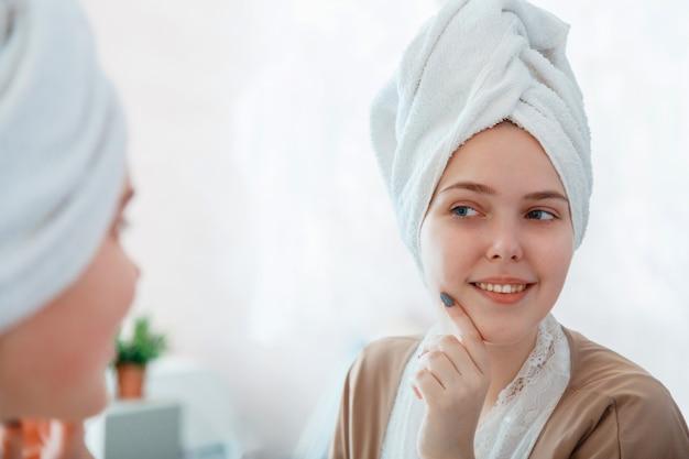 Self care jako część porannej rutyny w łazience. portret uśmiechnięta młoda kobieta z idealną skórą w odbiciu lustrzanym po wzięciu prysznica przed makijażem z ręcznikiem na głowie.
